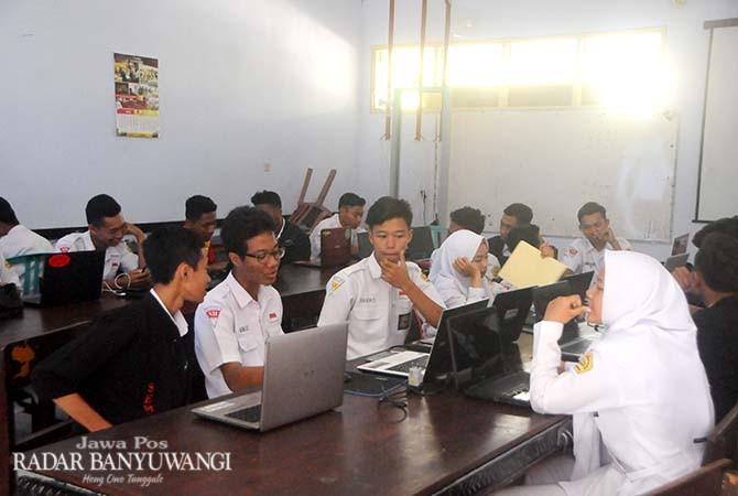 LAPTOP GELAP: Siswa jurusan TKJ SMKN 1 Glagah menanti listrik kembali menyala, Selasa (30/1).