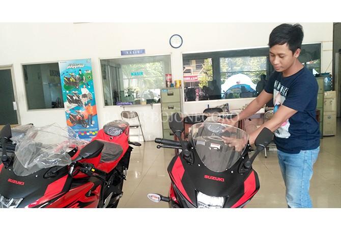 DIDOMINASI REMAJA: Salah satu konsumen saat melihat tipe terbaru motor sport produk Cina di sebuah diler di Lamongan.