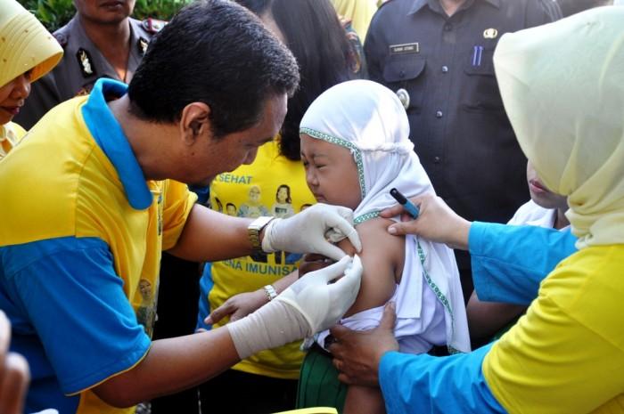 IMUNISASI: Kadinkes Kabupaten Kediri Adi Laksono saat melakukan imunisasi.