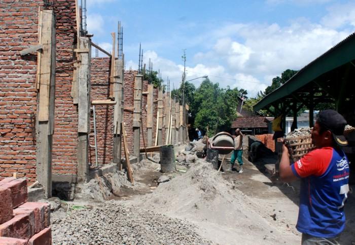 SIBUK: Pekerja sedang membangun ruko di sebelah timur Pasar Tempurejo, Kecamatan Pesantren.