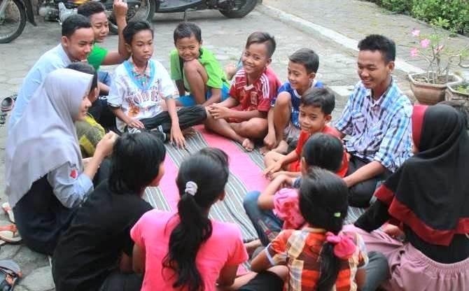 SEADANYA: Komunitas Pos Pelangi mengajak anak-anak Dusun Bedingin, Desa Sukorejo, Kecamatan Loceret bermain. Mereka juga mengajari anak-anak belajar sembari lesehan di tikar.