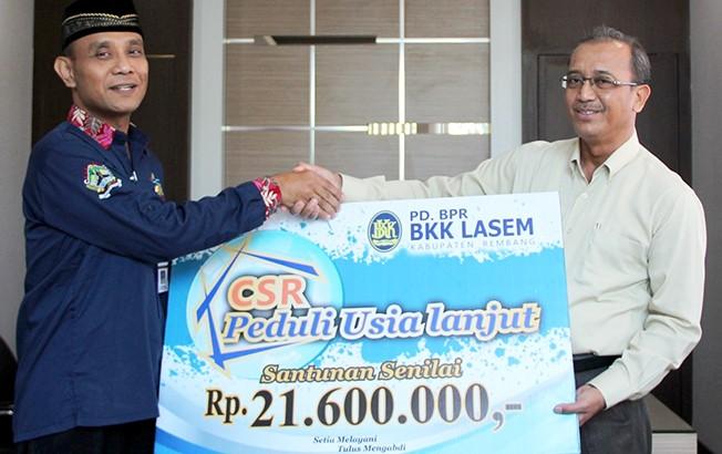 PEDULI LANSIA: Direktur Utama PD BKK Lasem Sutarjo (kanan) secara simbolis menyerahkan bantuan untuk lansia kepada perwakilan Dinsos PPKB Kabupaten Rembang.