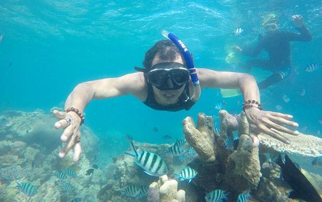 TAK MENYENTUH KARANG: Wartawan Jawa Pos Radar Kudus Baehaqi melakukan snorkeling di atas terumbu karang dan kerumunan ikan di sekitar Pulau Menjangan Kecil, Karimunjawa, Jepara.