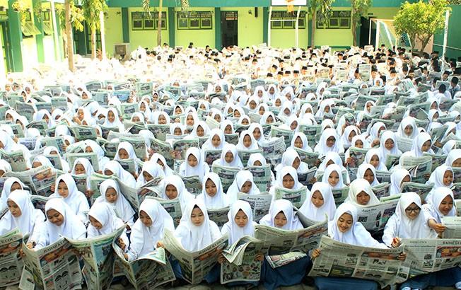 LITERASI: Siswa-siswi MA Nurul Ulum membaca koran Jawa Pos Radar Kudus di madrasah setempat Senin (24/9) kemarin. Kegiatan itu bagian dari literasi di sekolah itu.