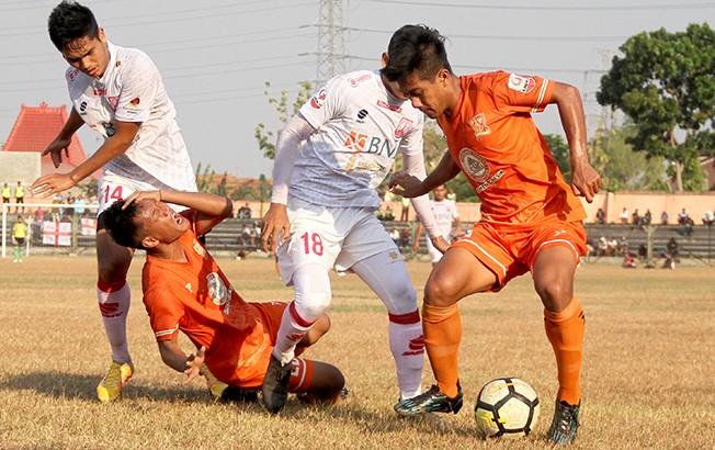 KERAS: Pemain PSIR Rembang Zaenal Arifin mempertahankan bola dari permainan keras pemain belakang Persis Solo saat berlaga di Liga 2 di Stadion Wilis Madiun, Minggu (7/10).
