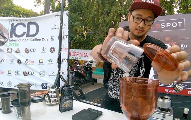 KOMODITAS ASLI JEPARA: Salah satu barista menggrinder kopi Tempur saat acara peringatan International Coffee Day (ICD) di Alun-alun Jepara baru-baru ini.