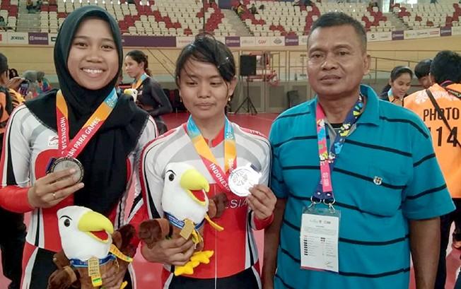 HARUMKAN NAMA BANGSA: Sri Sugiyanti atlet Para Cyling bersama ayah dan Kades Sengonwetan, Kecamatan Kradenan, Kabupaten Grobogan, usai pertandingan kemarin.
