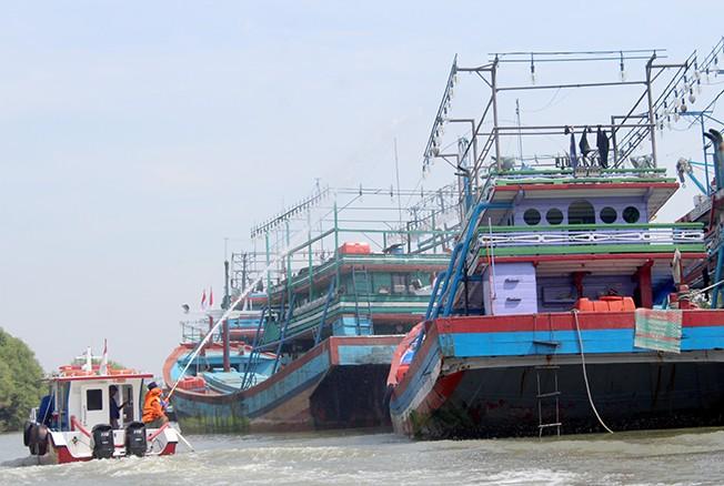 PARKIR: Beberapa petugas mengatur kapal yang semakin padat baru-baru ini. Solusi untuk mengurai kepadatan kapal salah satunya pembangunan tambat kapal.