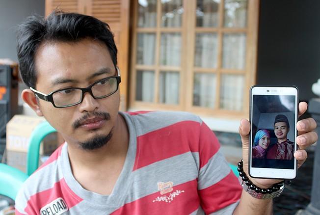 BERDUKA: Sepupu korban, Dwi menunjukkan foto korban bersama istrinya di kediaman orang tua korban di Desa Sitiluhur, Gembong, Pati, kemarin.