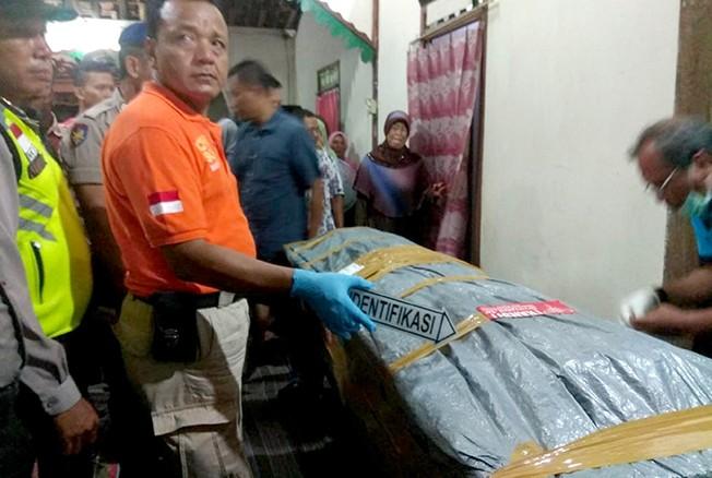 DIPERIKSA: Tim Inafis Polres Pati memeriksa jenazah korban saat tiba di Juwana pada Rabu (31/10) malam.