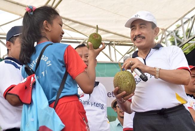 LESTARIKAN LOKALAN: Bupati Haryanto memberikan kuis kepada anak-anak mengenai sumber bahan pangan lokal di Festival Pangan Lokal di Alun-alun Simpang Lima Pati kemarin pagi.