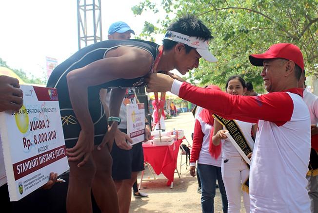 JUARA: Wakil Bupati Jepara (kanan) mengalungkan medali kepada para pemenang Jepara International Triathlon (JIT) 2018 di kawasan Pantai Tirto Samudera Bandengan kemarin.