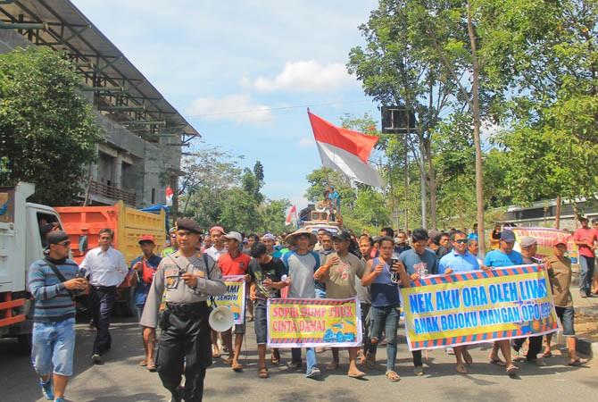 Ratusan massa long march menuju gedung DPRD sambil mengusung sejumlah spanduk.