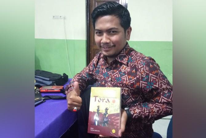 BERBUDAYA: Humas Politeknik Negeri Madura (Poltera) Taufik Hidayat memperlihatkan buku Tora; Satengkes Carpan Madura yang dibacanya, Rabu (11/4).