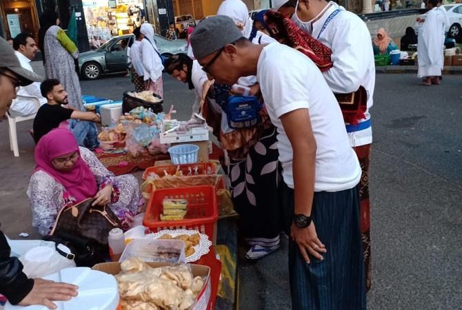 LARIS MANIS: Ketua Kloter 11 jamaah haji asal Sumenep Ibnu Hajar (kaus pendek putih) saat berbelanja jajanan khas Madura di Makkah, Rabu (1/8).