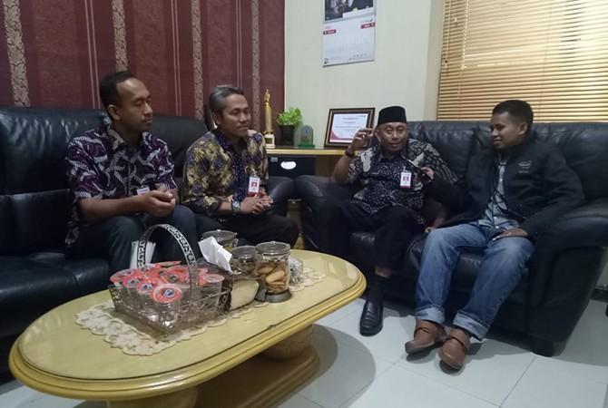 SANTAI: PimpinanBank Jatim PamekasanM.M.ArifFirdausi (berkopiah) didampingi dua pegawai Bank Jatim saat diwawancarai wartawan Jawa Pos Radar Madura di ruang kerjanya kemarin.
