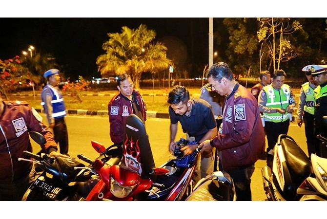 GELAP: Polisi memeriksa pengendara motor dan mobil di jalan raya akses Suramadu dini hari.