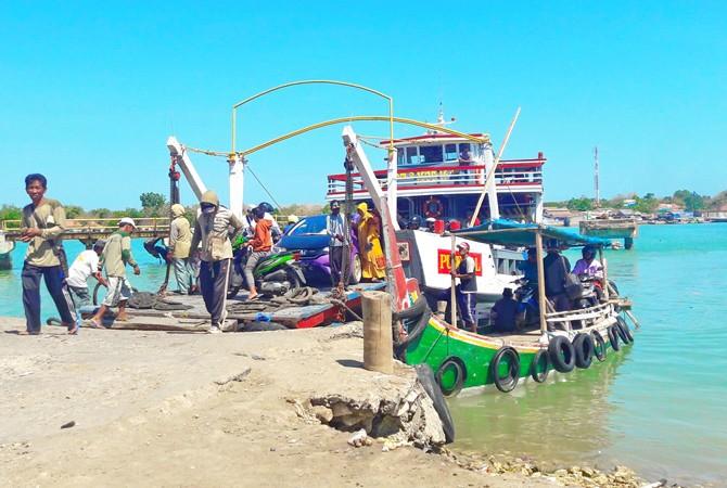 MENYEBRANG: Sejumlah penumpang keluar dari kapal tongkang yang melayani penyeberangan antara Kecamatan Kalianget–Talango.