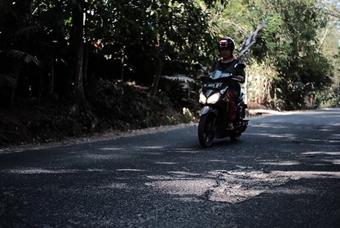 RINDANG: Pengendara melintas di jalan raya Desa Bilaporah, Kecamatan Socah, Bangkalan yang berlubang.