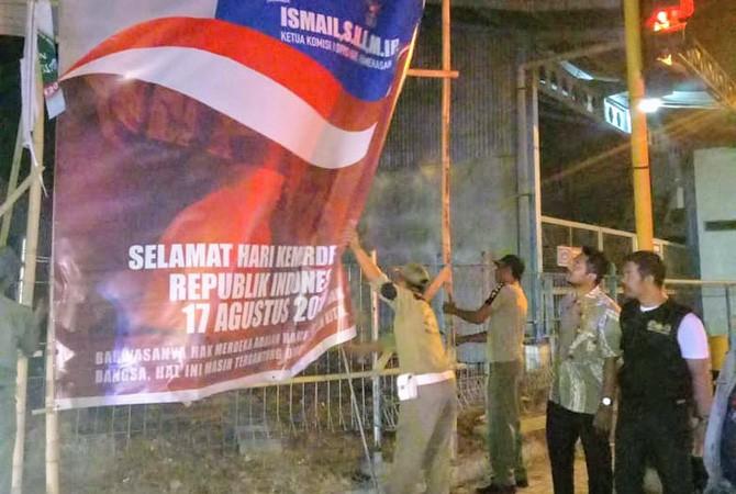 TEGAS: Satpol PP didampingi anggota Bawaslu dan Polres Pamekasan menurunkan banner yang dinilai melanggar di Jalan Trunojoyo, Kota Pamekasan, Senin malam (10/9).