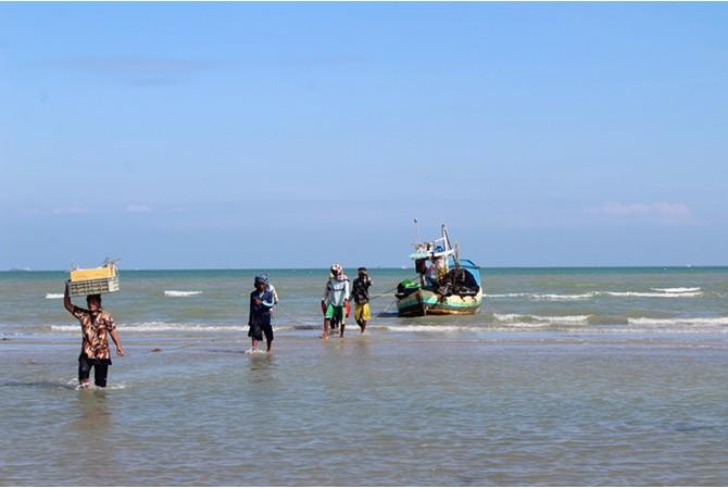KERJA KERAS: Warga menyunggi hasil tangkapan ikan nelayan di pantai Desa Dharma Camplong, Kecamatan Camplong, Sampang, kemarin.