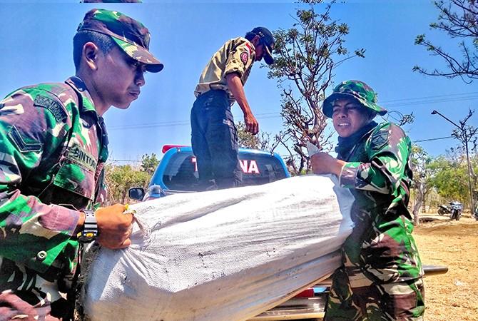 BELUM DISALURKAN: Anggota TNI, Polri, dan relawan menurunkan logistik dari kendaraan angkut ke posko bantuan di Pulau Sapudi, Sumenep.