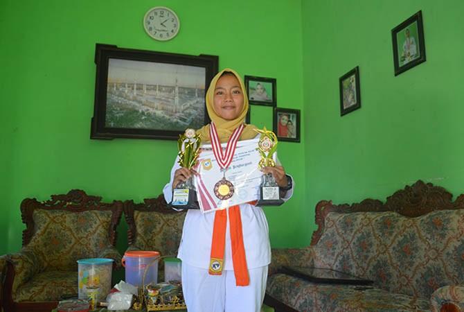 SEMANGAT: Sitti Faizeh, siswi dengan segudang prestasi menunjukkan hadiahnya di rumahnya pada Senin (22/10).