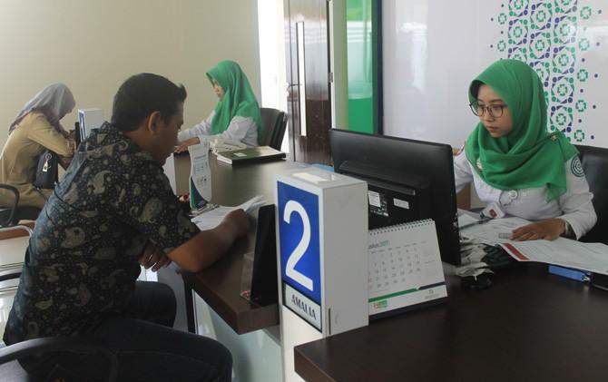 Warga melakukan pendaftaran JKN-KIS di Kantor BPJS Kesehatan Cabang Mojokerto.