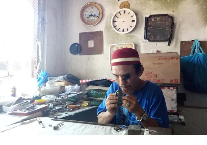 Suyadi menyelesaikan pekerjaan jam rusak milik pelanggan di lapaknya.