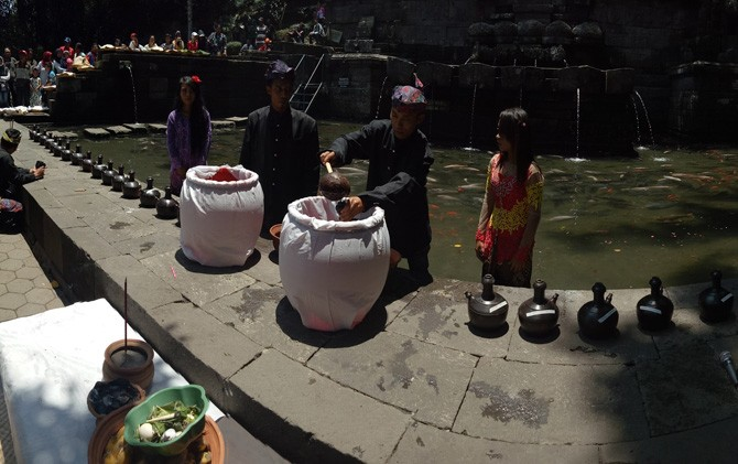 Pemangku adat memasukkan air suci dalam kendil dalam ruwat tirta di Petirtaan Jolotundo, Trawas, Mojokerto.