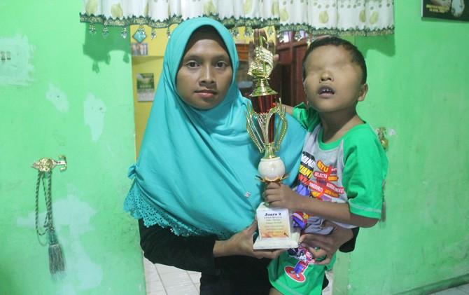 Azzam Nur Mu'jizat digendong ibunya, Solikhatin Munawaroh, sambil membawa tropi juara menyanyi tingkat Provinsi Jatim.