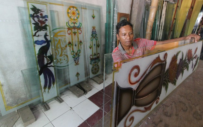 Akhmad Mukhlas melakukan finishing kaca hias dengan motif flora.