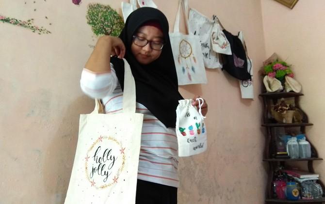 Puspita Amalia Sari menunjukkan hasil kreasi tas lukis di rumahnya Desa Mlirip, Kecamatan Jetis, Kabupaten Mojokerto.