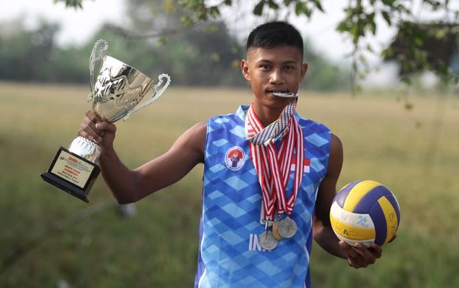 Bintang Akbar mengangkat trofi dan menunjukkan medali raihan prestasinya.