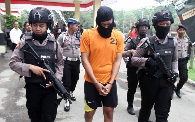 Dimas (tengah) digelandang petugas di Mapolres Mojokerto usai resmi ditetapkan sebagai salah satu tersangka aborsi.