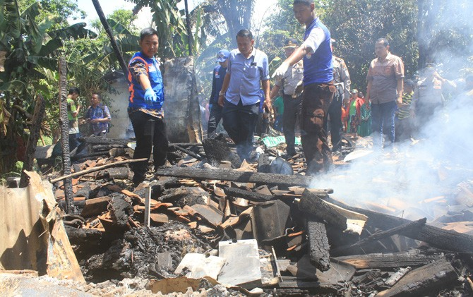 Petugas kepolisian bersama tim relawan menunjukkan lokasi tubuh korban yang terbakar bersama rumahnya di Kelurahan Pulorejo, Kec. Prajurit Kulon, Kota Mojokerto.