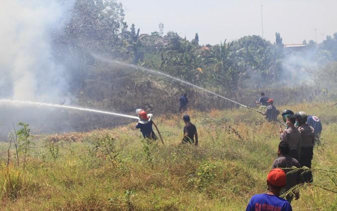 Petugas PMK berjibaku memadamkan api yang membakar semak belukar di Lingkungan Pekayon, Kelurahan/Kecamatan Kranggan, Kota Mojokerto.