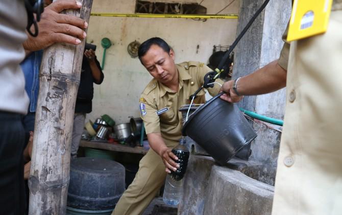 Petugas Dinas ESDM Provinsi Jatim mengambil sampel air di sumur milik warga di Dusun Panjer, Desa Tunggalpager, Kecamatan Pungging, Kabupaten Mojokerto, Senin (22/10).