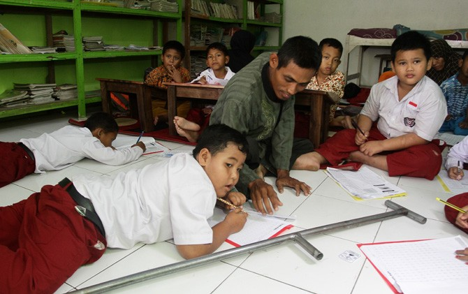 Seorang relawan memberikan bimbingan siswa SD Inklusi Nurul Islam Sumengko, Kec. Jatirejo, Kabupaten Mojokerto.