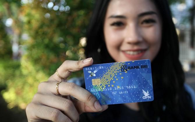 Seorang nasabah BRI menunjukkan kartu ATM BRI yang baru.