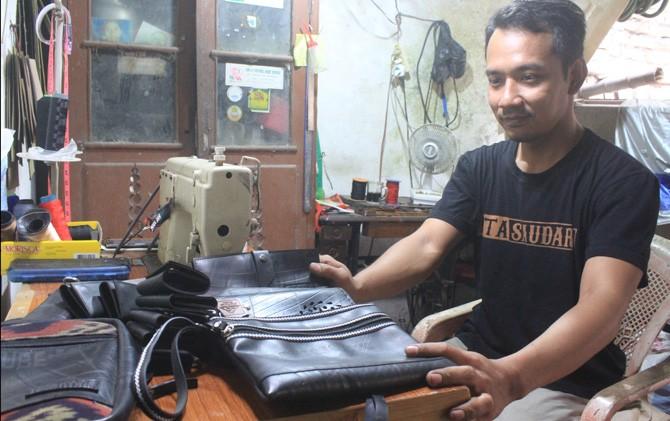 Andres Filtra saat menjahit ban bekas untuk disulap menjadi aneka tas di rumahnya di Desa Salen, Kecamatan Bangsal, Kabupaten Mojokerto.