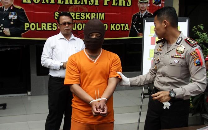 Kapolresta Mojokerto AKBP Sigit Dany Setiyono memegang tersangka Muh. Aris saat pers rilis.