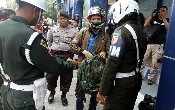 Petugas Denpom Mojokerto saat memeriksa pengendara yang membawa atribut TNI di Jembatan Timbang Trowulan, Mojokerto.