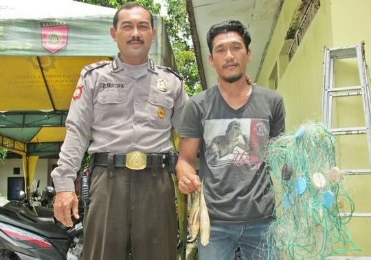 Tersangka M. Rosihin diamankan petugas beserta barng bukti jaring dan  ikan hasil curiannya.