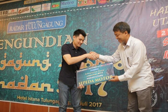 PERWAKILAN : Direktur Jawa Pos Radar Tulungagung Wahyudi Novianto menyerahkan hadiah simbolis sepeda motor kepada pemenang yang diwakili toko Hero.