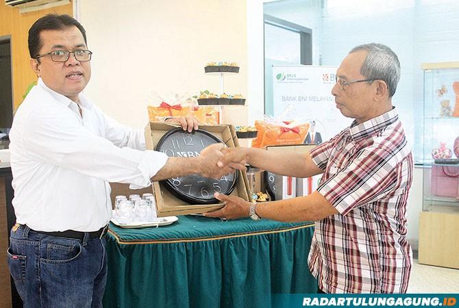 SEMOGA BERMANFAAT: Pemimpin Bidang Pelayanan Budoyo Yanto memberikan suvenir kepada salah seorang nasabah BNI.