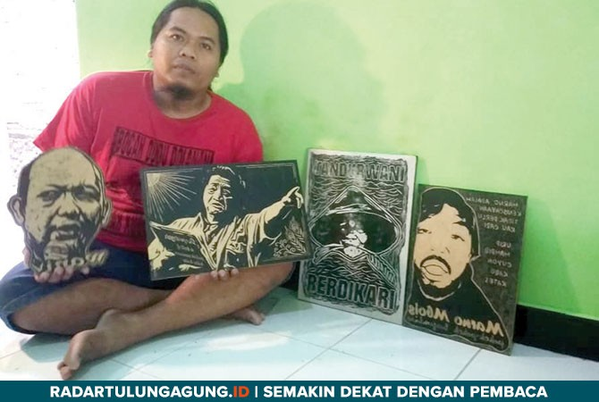 TELATEN: Nanang Wahyudianto saat memperlihatkan hasil seni grafis cukil kayu kemarin (24/10).