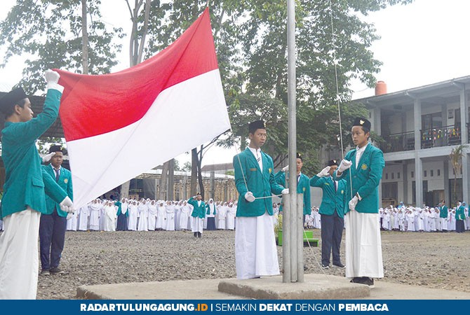KHIDMAT: Pasukan pengibar bendera mengibarkan Sang Merah Putih pada upacara peringatan HSN, Senin (22/10).