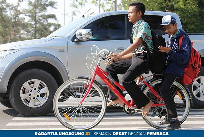 NYANTAI: Dua pelajar SMP berboncengan mengendarai sepeda sekolah warna merah saat pulang sekolah di Jalan Soedanco Supriadi, kemarin (31/10).