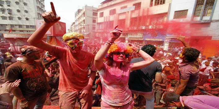 Foreign tourists daubed in colours dance as they celebrate Holi in the northeastern Indian city of Guwahati March 27, 2013. Holi, also known as the Festival of Colours, heralds the beginning of spring and is celebrated all over India. REUTERS/Utpal Baruah (INDIA - Tags: RELIGION SOCIETY TRAVEL)